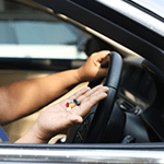 Women taking pills inside his car while driving